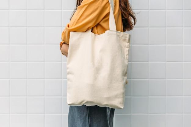 女性はバッグキャンバス生地を保持しています。 Premium写真