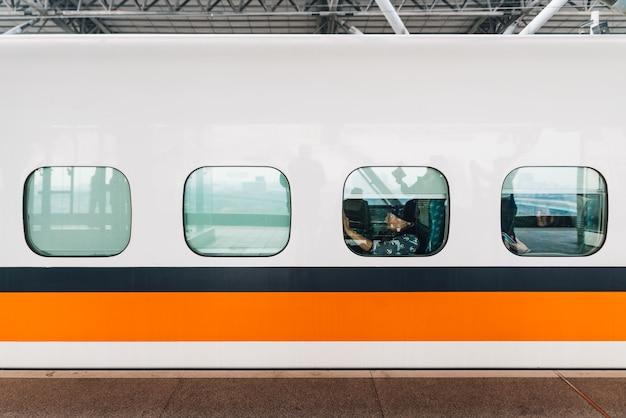 台湾高速列車、オレンジと青のストライプの白い列車の側面図です。 Premium写真