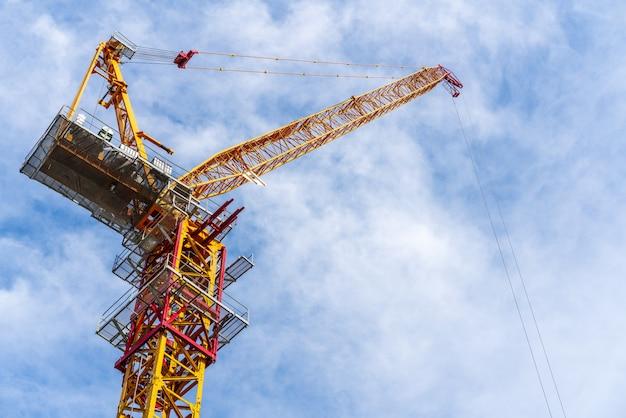 バックグラウンドで雲と青空と工事現場で働くクレーン。 Premium写真