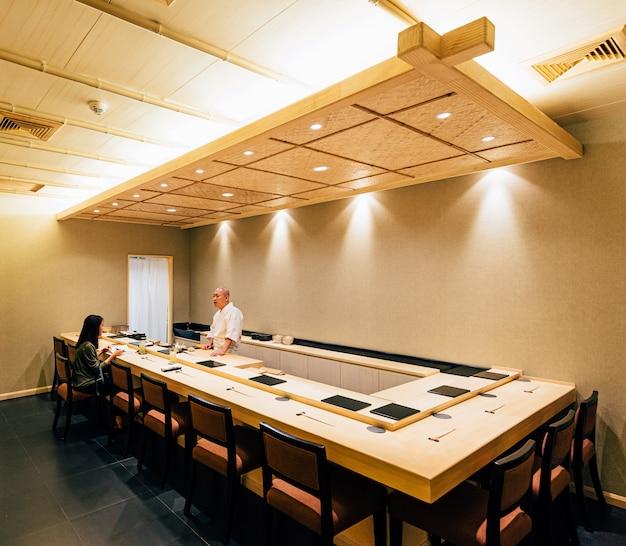 木で飾られた日本のおまかせレストラン。キッチンカウンターでシェフが料理をし、直接お客様に仕えます。 Premium写真