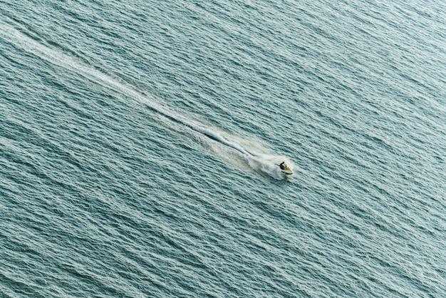 海面に水のしぶきと海の上のジェットスキーをなくして男。 Premium写真