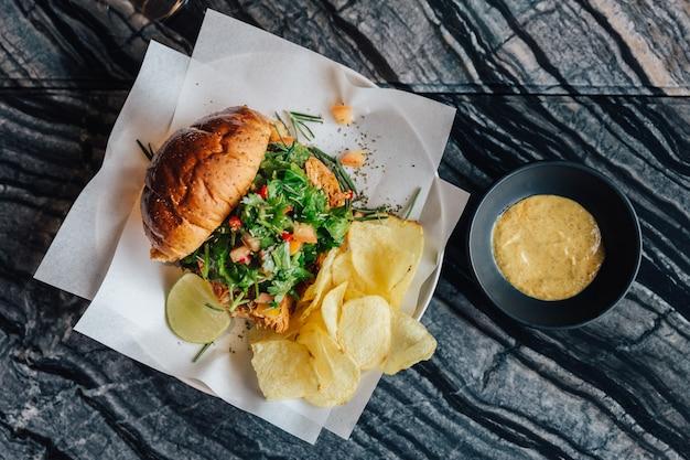 ローストチキンサラダハンバーガーのトップビューチップとマスタードソース添え大理石の上のテーブル。 Premium写真