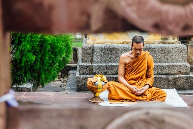 Индийский буддийский монах в медитации возле дерева бодхи возле храма махабодхи Premium Фотографии