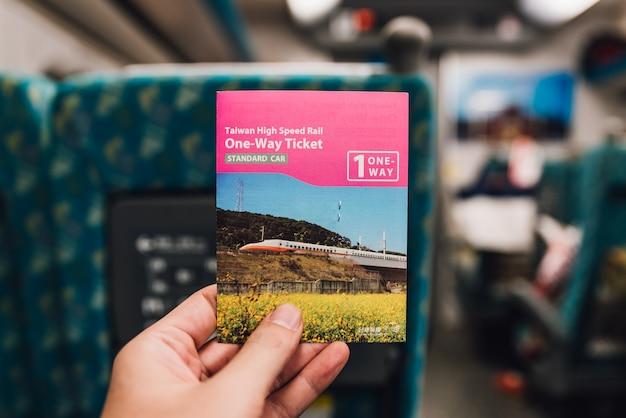 台湾、台北のプラットフォームで台湾高速列車のチケットを持っている手。 Premium写真