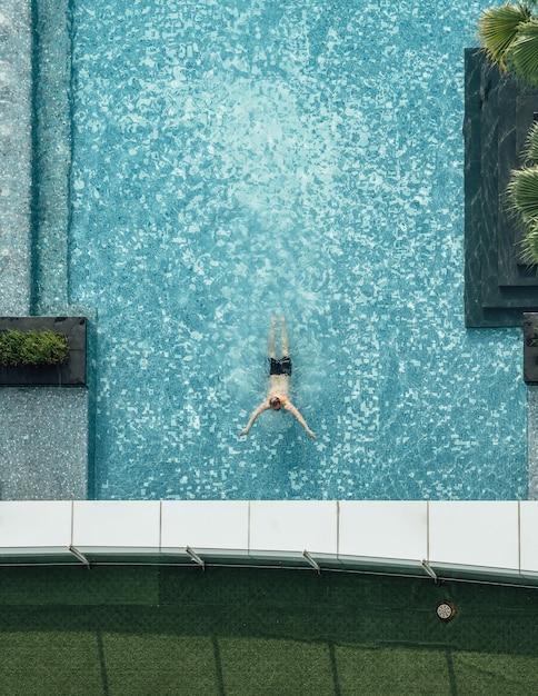 フローティングバーと夏に泳ぐ男とスイミングプールの平面図です。 Premium写真