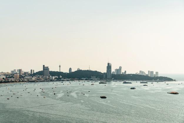 建設建物のある街並みとボート、パタヤビーチの明るい空と海のパノラマ。 Premium写真