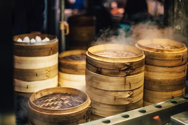 積み重ねた竹の蒸し器の山は点心で蒸している。 Premium写真