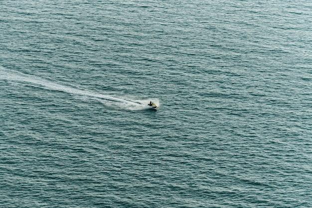パタヤビーチの近くの海の表面に水のしぶきと海でジェットスキーをなくす男。 Premium写真
