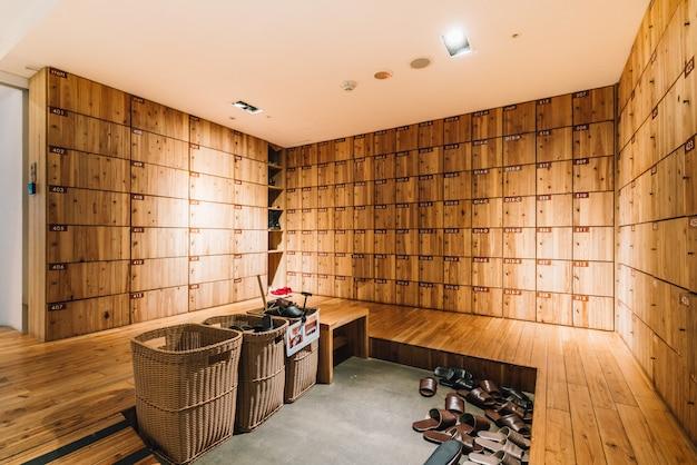 ホステルのレセプション内に木製の靴ロッカー。台湾の台北にあるモダンで控えめでクリーンなデザイン。 Premium写真