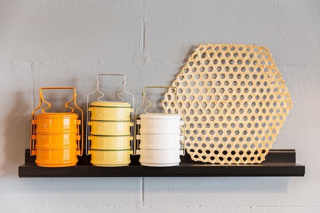 木製の棚にティフィンのオレンジ、黄色、白のスチール製フードキャリア。タイ風のポーションサイズ。レストランの装飾。 Premium写真