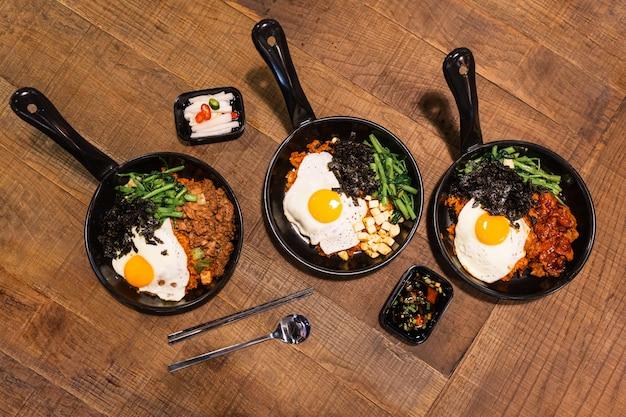 熱い鍋にビビンバの平干し(キムチポーク、豆腐、海苔、炒め野菜を混ぜた韓国の米)。 Premium写真
