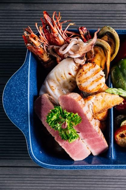 魚、イカ、エビ、ムール貝などのグリルを混ぜたシーフードのトップビュー。 Premium写真