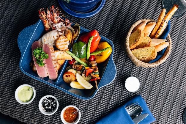 魚、イカ、エビ、ムール貝、野菜などのグリルを混ぜたシーフードのトップビュー。 Premium写真