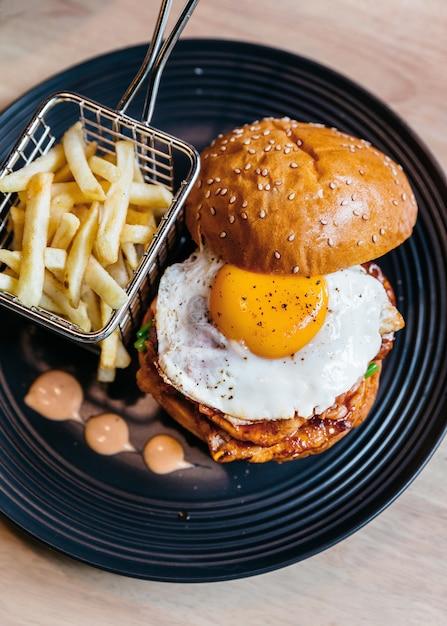 揚げた卵とおいしいハンバーガーのトップビューは、木製のテーブルの黒いプレートにフライドイ添え。 Premium写真