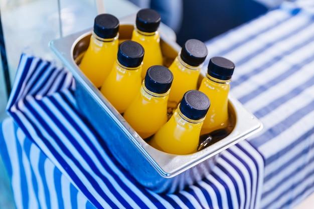 冷たいオレンジジュースボトル白と青のストリップファブリック上のアルミボックス。 Premium写真