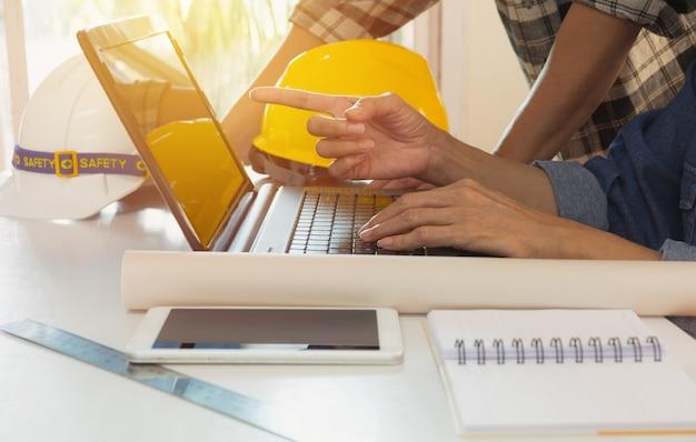 ラップトップを使用して、テーブルの上に黄色のヘルメットとラップトップを使用する建築家のエンジニア。 Premium写真