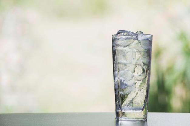 アイスキューブと自然の背景を持つテーブルの上のガラスの水 Premium写真