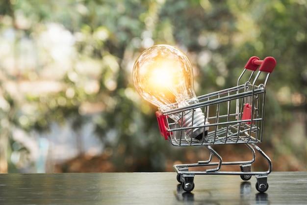 ショッピングカート金融とショッピングのコンセプトを持つ省エネ電球 Premium写真