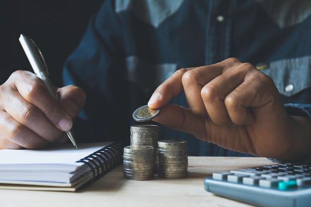 手はビジネスのために成長しているお金コインスタックでコインをドロップします。 Premium写真