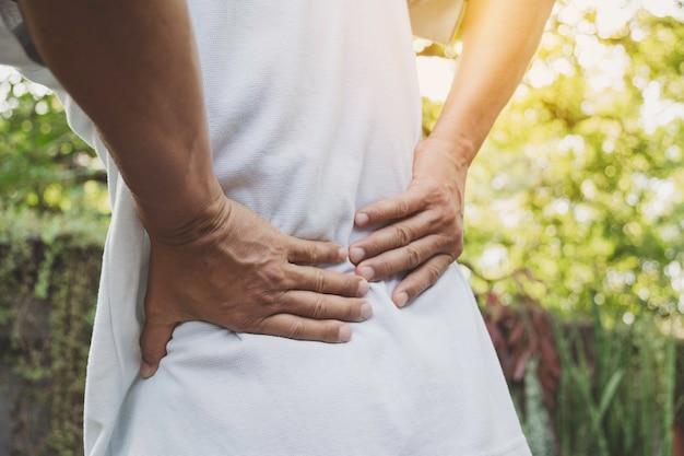 屋外で腰痛、脊髄損傷および筋肉問題に苦しんでいる人。 Premium写真