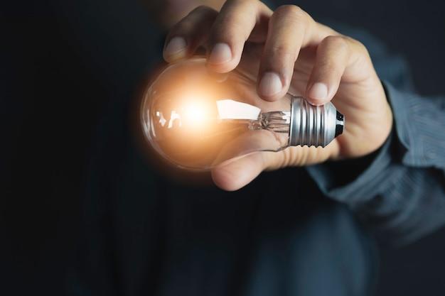 手の革新的または創造的な概念は、挿入テキストの電球とコピースペースを保持します。 Premium写真