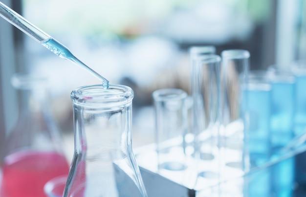 分析、医療、製薬、科学研究の概念のための液体のガラス実験室化学試験管を持つ研究者。 Premium写真