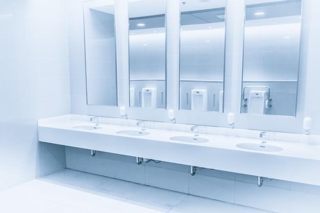 バスルームの清潔で新しいモダンインテリアトイレのシンク行青い色調水ハンドシャワー Premium写真