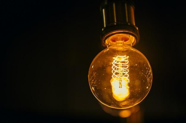 Одиночная лампочка на темной предпосылке с космосом для текста. Premium Фотографии