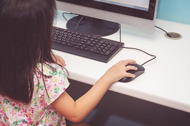 Девушка играет с компьютером Premium Фотографии