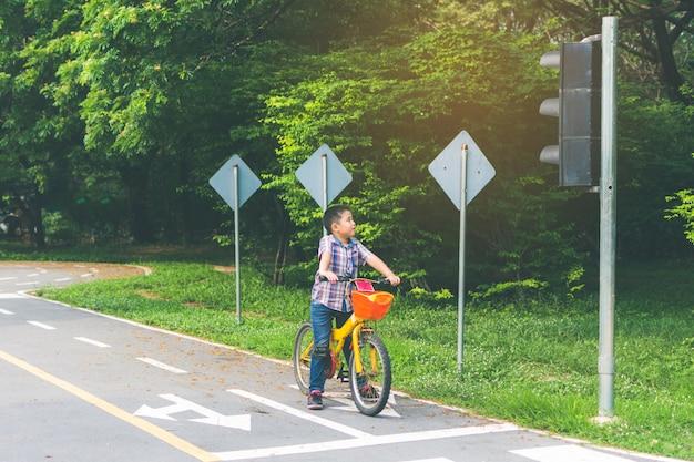 Мальчик катается на велосипеде в парке, остановки велосипеда на светофорах Premium Фотографии