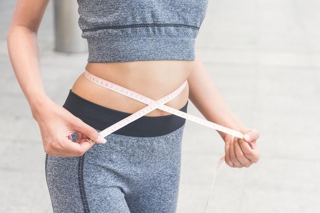若い女性が巻尺で彼女の腰を測定 Premium写真