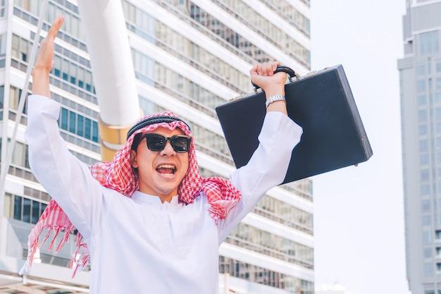 街で両手を上げることによって立っているアラブのビジネスマン Premium写真