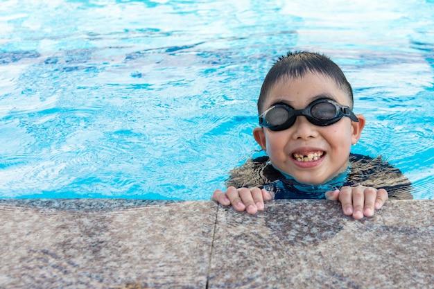 Молодой мальчик, плавание в бассейне. Premium Фотографии