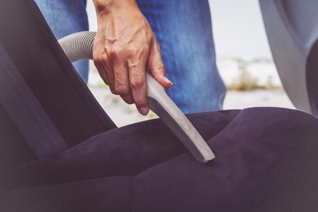 掃除機で車内を掃除する人 Premium写真