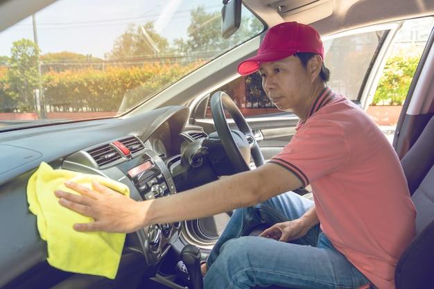 自動車サービススタッフがマイクロファイバーの布で車を清掃 Premium写真
