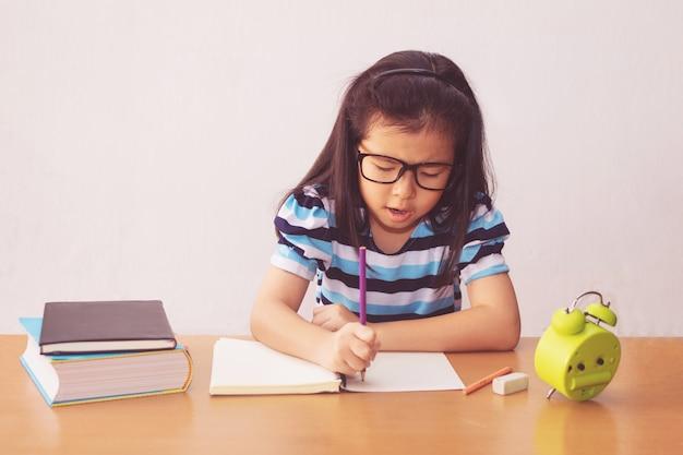 テーブルの上の本を書くアジアの少女 Premium写真
