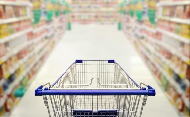 空っぽのショッピングカートショッピングコンセプトとスーパーマーケットの抽象的なぼやけた写真。 Premium写真