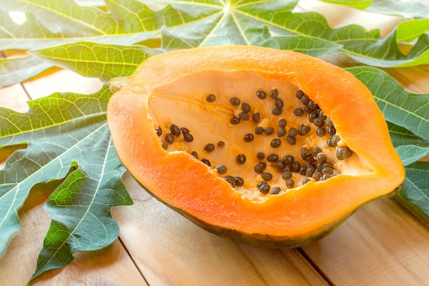 Спелая папайя на деревянный стол, спелая папайя польза для здоровья. Premium Фотографии