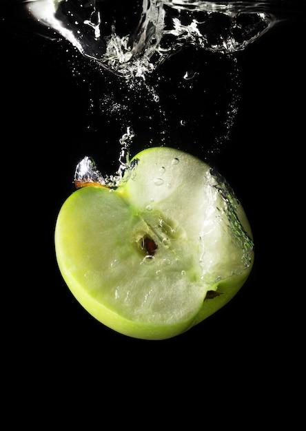 水に落ちる青リンゴ Premium写真