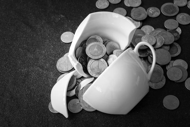 Чашка была только что разбита на кусочки, а вокруг нее разбросаны монеты Premium Фотографии