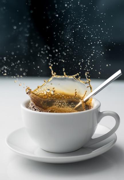 白いカップのコーヒーのスプラッシュ Premium写真