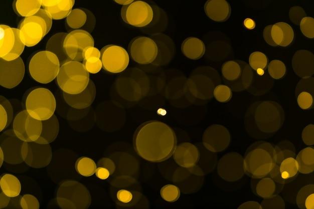キラキラヴィンテージライトの背景。ダークゴールドとブラック。デフォーカス Premium写真