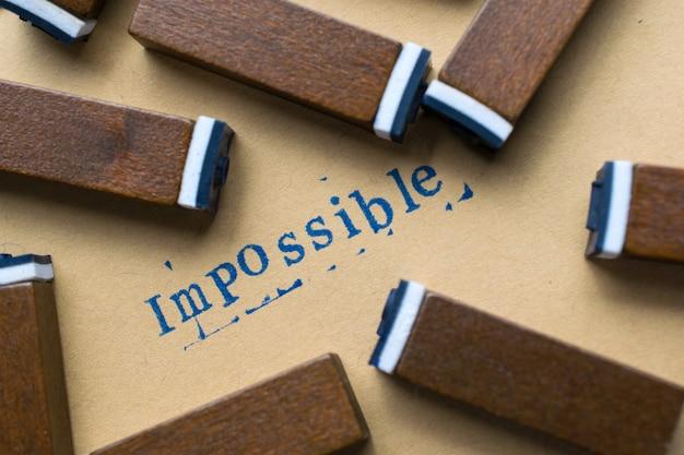 不可能な概念の背景の紙の上のスタンプ文字フォントから不可能なアルファベット文字単語 Premium写真