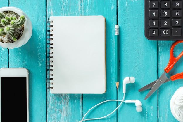 スマートフォン、ノートブック、鉛筆と花、木の机の上の平面図フラット。 Premium写真