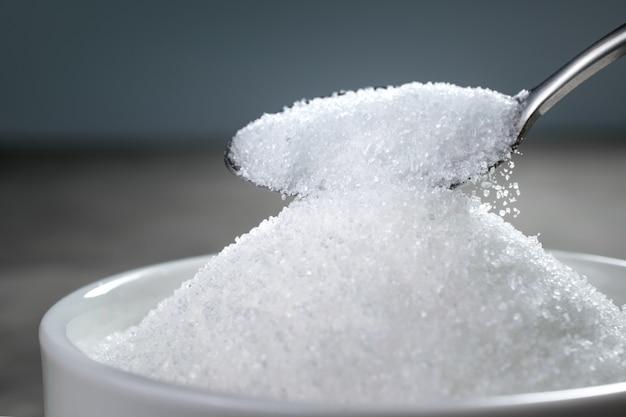 スプーンからボウルに砂糖が注がれている。 Premium写真