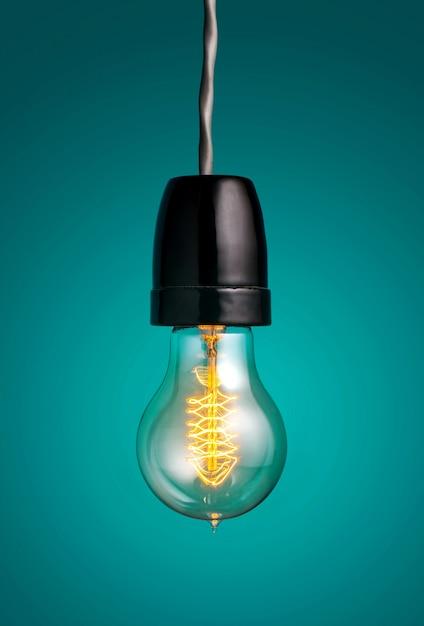 Античные лампочки накаливания стиля эдисона вися электрическую лампочку над зеленой предпосылкой. Premium Фотографии