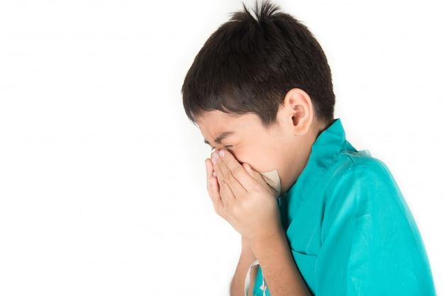 Маленький мальчик чихает и кашляет от гриппа с использованием чистой ткани Premium Фотографии