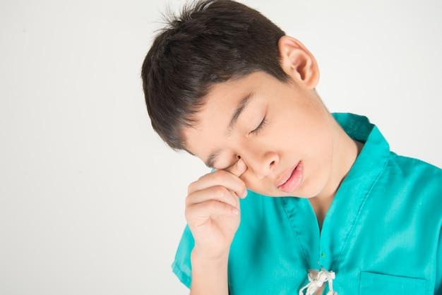 小さな男の子は指の傷で目の痛みがあります Premium写真