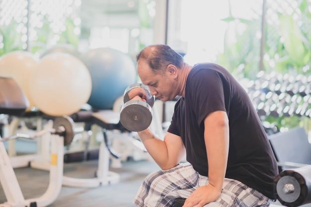 アジア人男性がジムの減量で運動を行う Premium写真