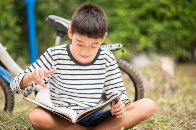 Книга чтения мальчика сидя с велосипедом в парке Premium Фотографии